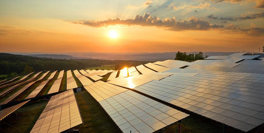 Solarpark mit Sonne im Hintergrund